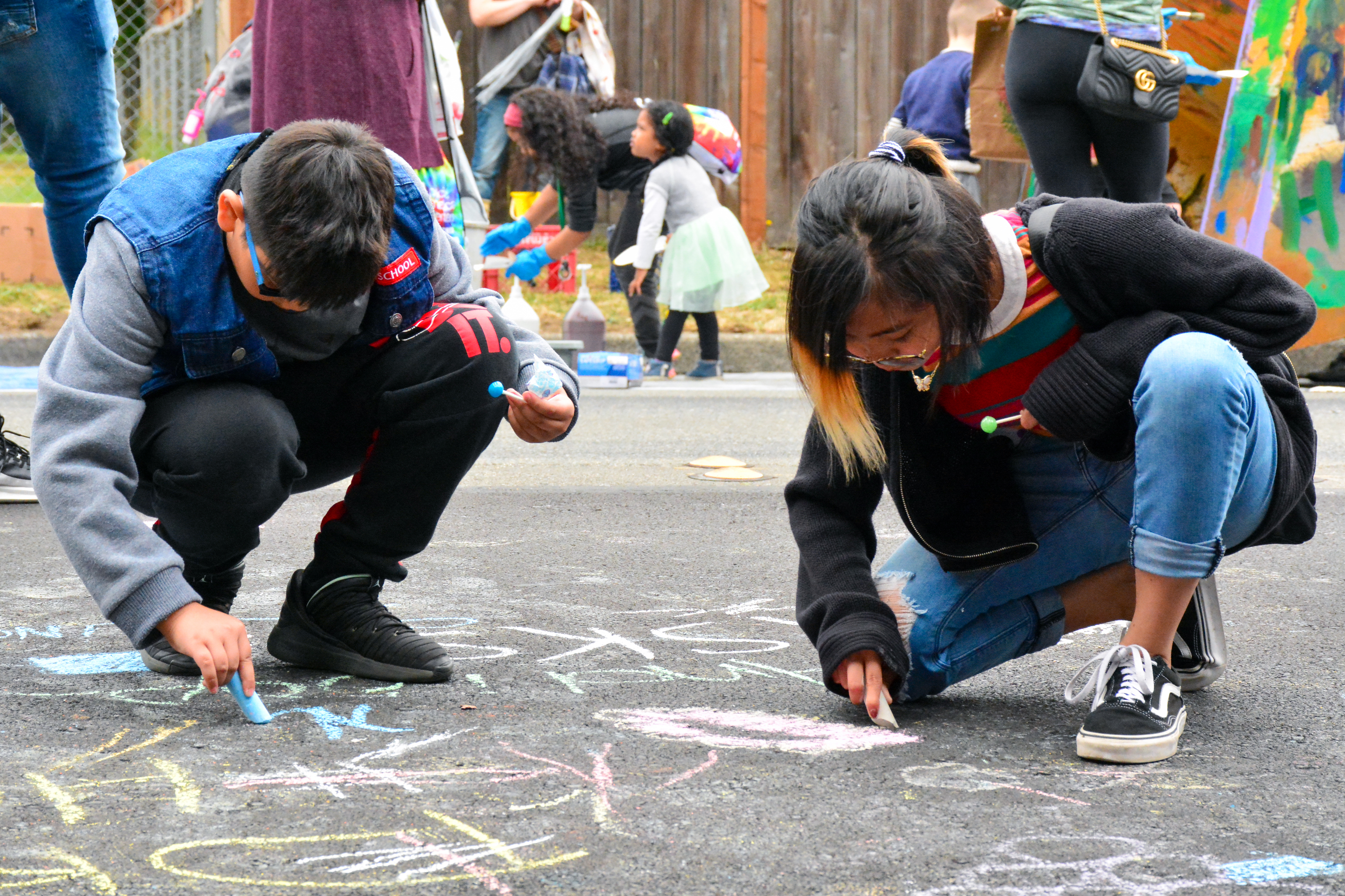 Kids create art with chalk on asphalt