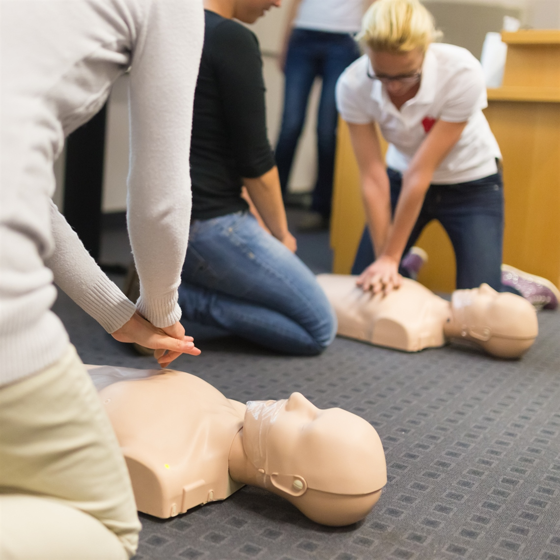 Adults practicing giving CPR on a dummy