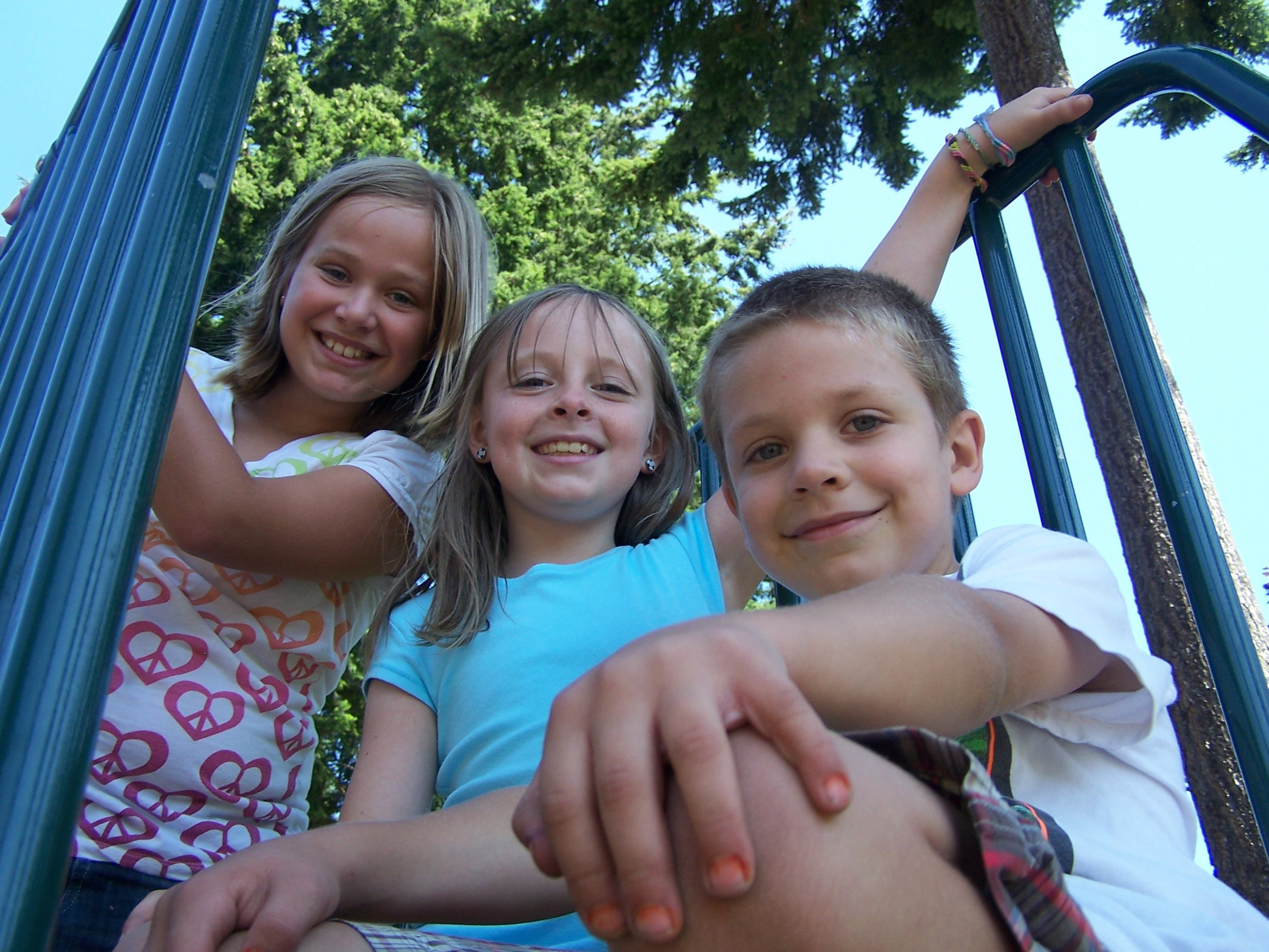 Two girls and boy at the top of playground slide
