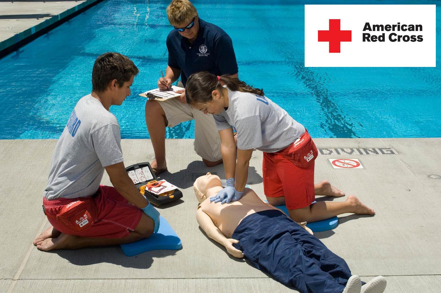 Lifeguards practicing CPR skills while instructor watches