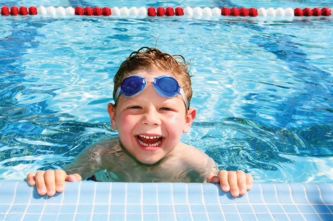 Boy holding on to side of the pool with a huge smile