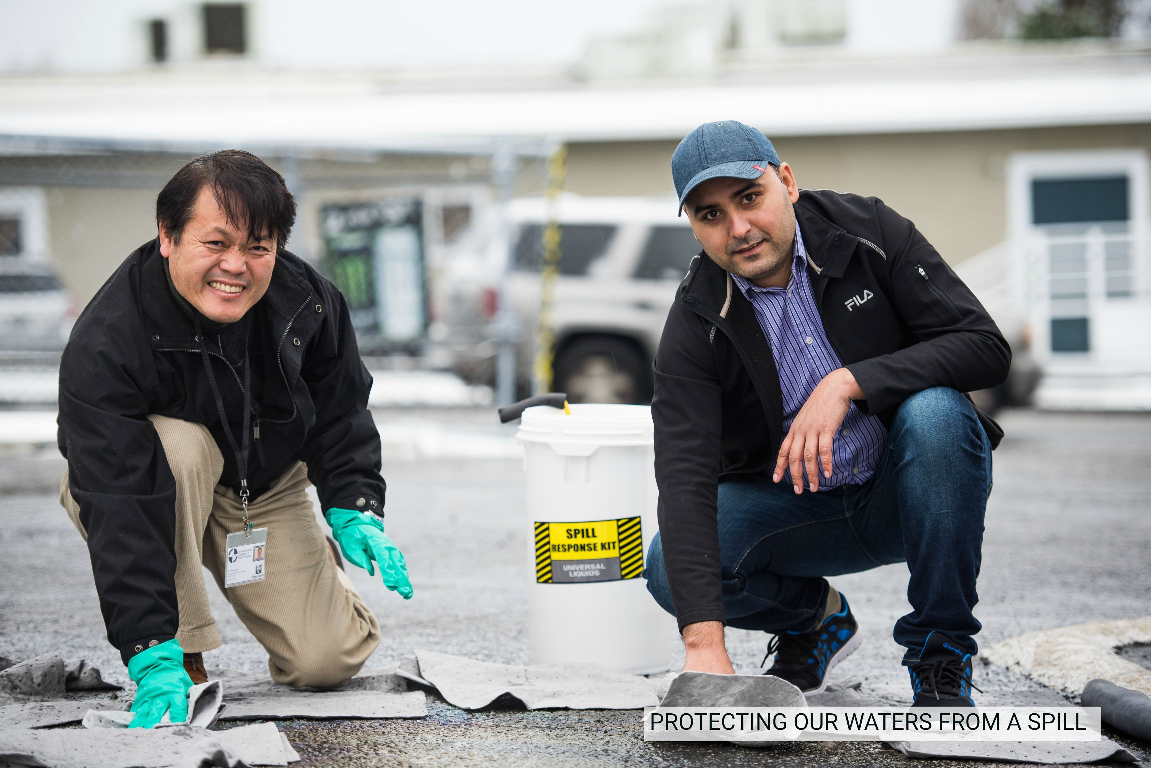 Two men cleaning up an oil spill with a spill kit