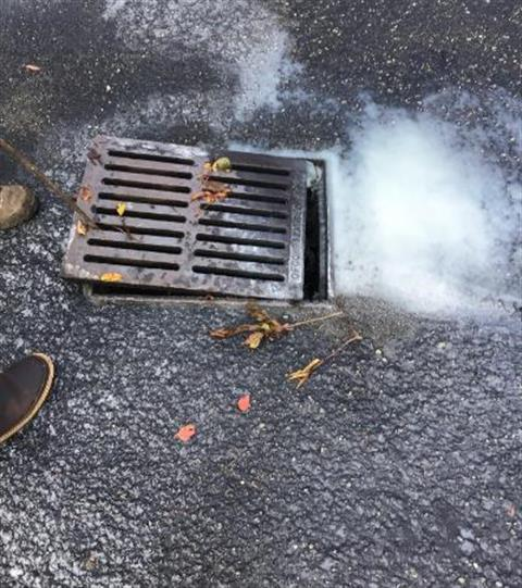 Storm drain with paint going into it